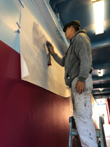 Bob Henry, mural restoration expert, doing final touch ups to the Mural Alley wall painting